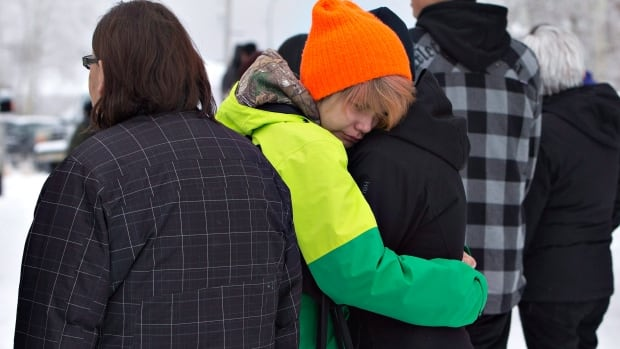 Church members console each other outside church after a mass in La Loche,  Sask., on Sunday, following the shooting on Friday.