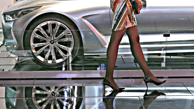 A woman walks by an auto display at the North American International Auto Show in Detroit. The auto industry is increasingly catering to women, focusing on more pragmatic features like safety, price and fuel economy.