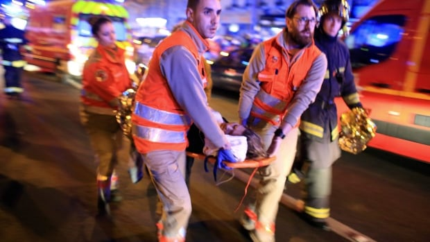 In this Nov. 13, 2015, photo, a woman is rushed from the Bataclan concert hall after gunmen attacked the venue in Paris. New video released Sunday by the Islamic State group purports to show the extremists who carried out Paris attacks.