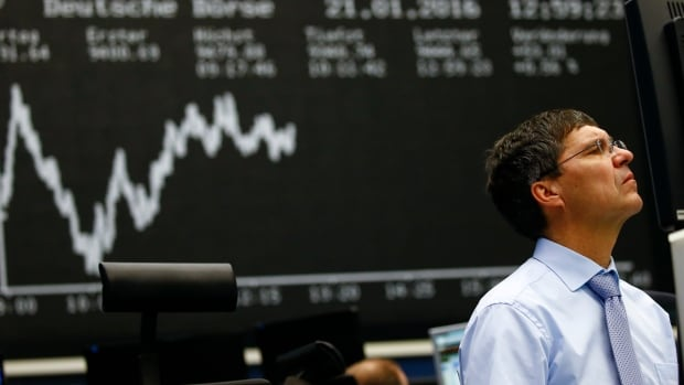 A trader works at his desk in front of the German share price index at the stock exchange in Frankfurt.
