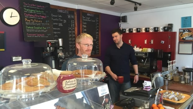 Owner Oliver Mahon (left) serves customers at the Darkside Gallery & Café. It has been charged with violating the land-use bylaw in Dartmouth.