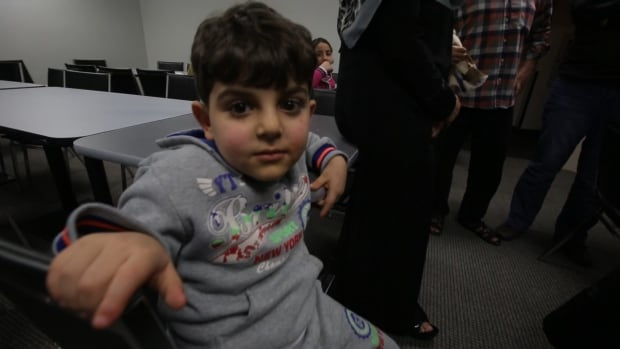 A young Syrian sits in a downtown hotel while he and his family wait for more permanent accommodation in Canada. Many Syrians say they are thankful to be in the hotel.