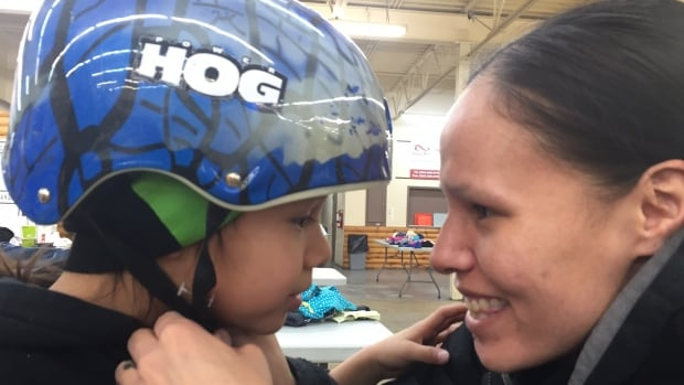 Derek Spence, 6, and his mother, Georgina Spence, try on a new-to-them helmet that they picked up at the Indian and Metis Friendship Centre on Monday.