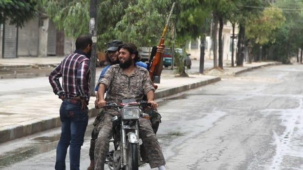 Free Syrian Army fighters on a motorbike chat with their friend in a rebel-controlled area of Aleppo, Syria on Aug. 30, 2015. Syrian opposition groups are meeting in Riyadh, Saudi Arabia to decide whether to attend UN-sponsored peace talks later this week.