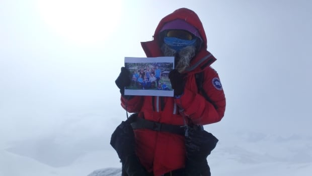Heather Moyse stands with a picture of her family on the summit of Vinson Massif.