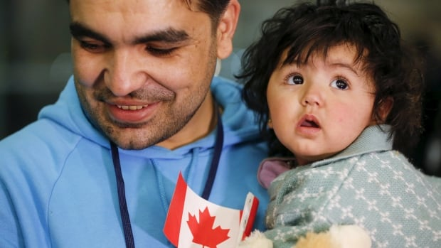 A Syrian refugee holds his daughter as they arrive at Pearson airport last month. A U.S. Senate committee will discuss Canada's 'fast-track' refugee plan next week.