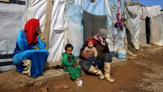 A Syrian family sit outside their tent, at a Syrian refugee camp, in the eastern town of Kab Elias, Lebanon, Wednesday, Jan. 27, 2016. Newly released government documents show the previous Conservative government cherry picked certain Syrian refugee files.