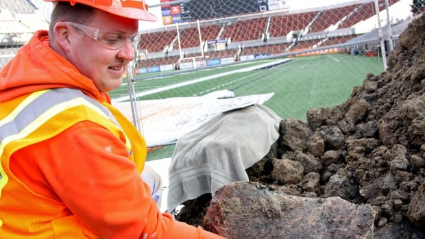 Woodburn High School science teacher Dave Ellingson holds part of the pelvis of a mammoth found at an Oregon State University construction site by a football field in Corvallis, Ore.