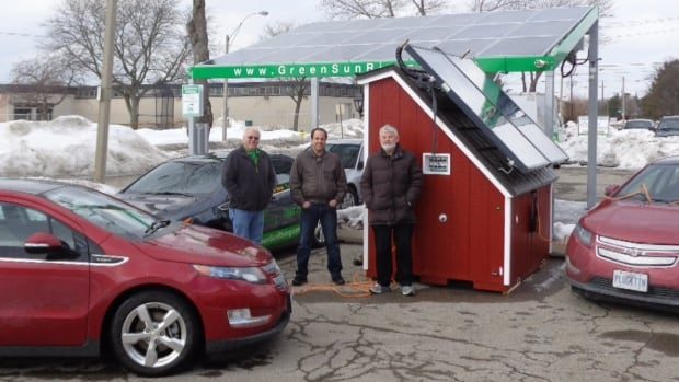 Michael Schneider, Pino Mastroianni and Paul Allsop of the Windsor Essex EV Association charge their cars at a solar charger built by Green Sun Rising.