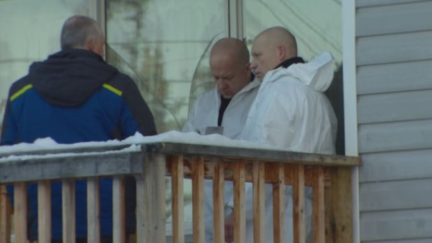 Investigators stand on the porch of a home in Whitehorse's McIntyre subdivision on Friday afternoon. Police and the Yukon coroner's office are investigating a sudden death.