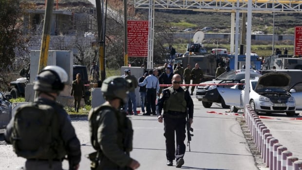 Israeli troops inspect the scene of the shooting at an Israeli checkpoint near the West Bank city of Ramallah.
