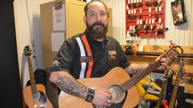 Jonny Aho, who is helping collect guitars for veterans, says a guitar is a 'good therapist.'