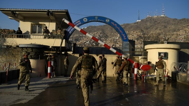 Afghan security personnel stand guard near the site of Monday's suicide attack at the entrance to a police base in Kabul.