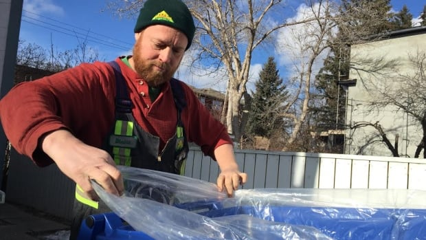 Blaine Armstrong of PEL Recycling drops off a bin and liner at an eight-plex in southwest Calgary.
