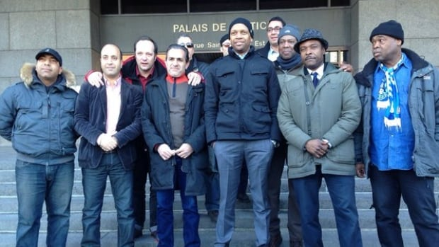 Taxi drivers stand outside the Montreal courthouse on Tuesday, where they filed an injunction against Uber.