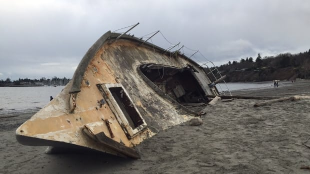 A large vessel with a concrete hull has been sinking into the beach in Cadboro Bay since it washed up in December. The municipality has decided to pay to remove it.