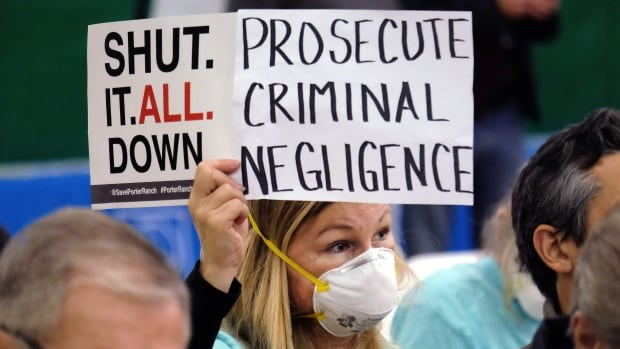 Tera Lecuona, resident of the heavily-impacted Porter Ranch area of Los Angeles, holds a protest sign during a January hearing in Granada Hills over a gas leak at Southern California Gas Company's Aliso Canyon Storage Facility.