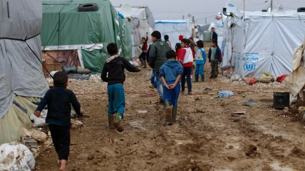 In this Monday, Jan. 4, 2016, file photo, Syrian refugee children walk in mud from the heavy rain at a refugee camp in the town of Hosh Hareem, in the Bekaa valley, east Lebanon. International aid to the victims of Syria's five-year-old war, including millions forced to flee their homes, has persistently fallen short, but organizers of the  annual Syria pledging conference hope for greater donor generosity.