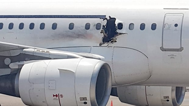 A hole can be seen in a plane operated by Daallo Airlines as it sits on the runway of the airport in Mogadishu, Somalia. A gaping hole in the commercial airliner forced it to make an emergency landing at Mogadishu's international airport late Tuesday.