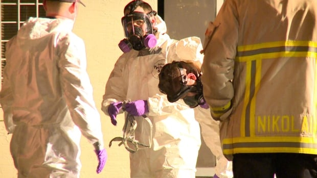 Vancouver firefighters begin to decontaminate, after unearthing a body that was partially buried in hoarded junk Wednesday night in Vancouver.
