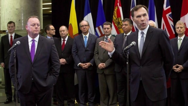 Finance Minister Bill Morneau, right, holds a news conference as his Saskatchewan counterpart Kevin Doherty, left, and provincial and territorial counterparts watch in Ottawa on Dec. 21, 2015. The ministers agreed to discuss CPP reform this year.