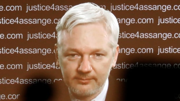 WikiLeaks founder Julian Assange is seen on a screen as he addresses journalists in London by video link from Ecuador's embassy in London on Friday in light of the UN ruling.