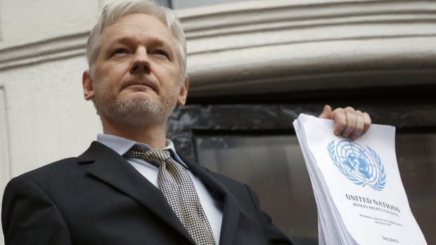 WikiLeaks founder Julian Assange holds a UN report as he speaks on the balcony of the Ecuadorean Embassy  in London on Friday.