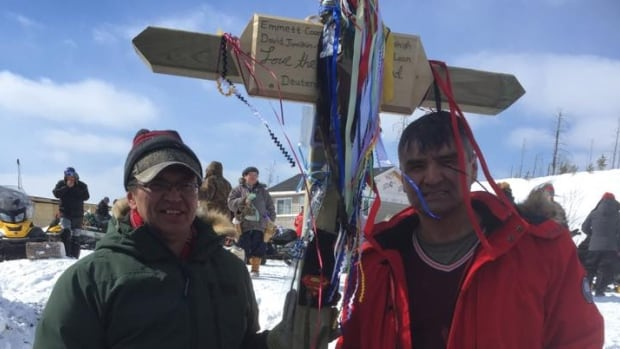 Jason Coonishish, left, and pilot Philip Petawabano stand with a cross erected at the site of the cabin fire at Bussy Lake.