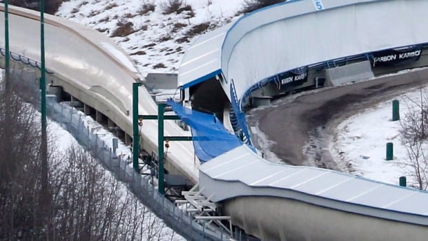 A tarp covers the intersection of the bobsled and luge tracks at Canada Olympic Park in Calgary. An after-hours incident at the luge-bobsled track early Saturday resulted in the deaths of two young men and left six others injured.