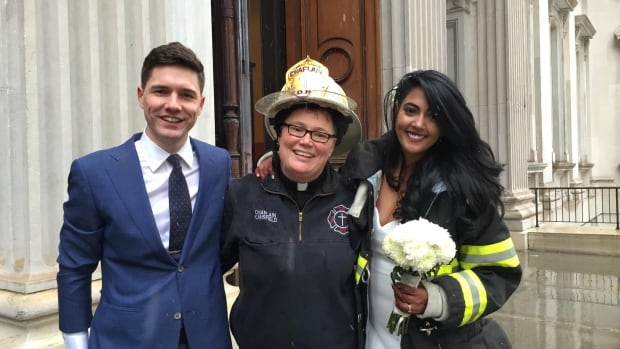 Newlyweds Aaron Vanderhoff and Nesh Pillay pose with Rev. Ann Kansfield (centre) the New York City Fire Department chaplain who officiated their wedding amid the chaos of a fatal crane collapse in Manhattan.