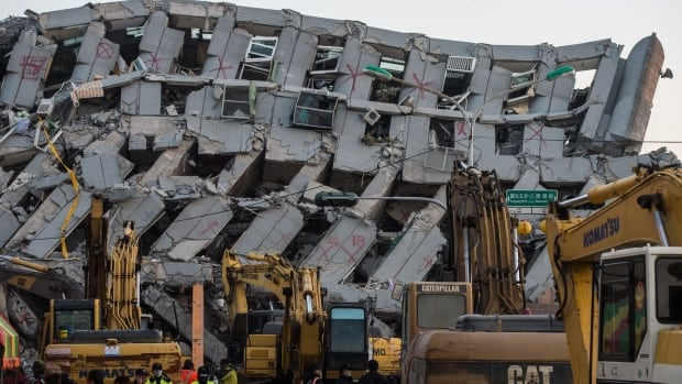 A general view shows excavator vehicles and rescue workers Tuesday in front of a building which collapsed in the 6.4 magnitude earthquake, in the southern Taiwanese city of Tainan.