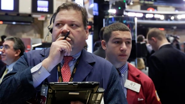 Trader John Santiago, foreground left, works on the floor of the New York Stock Exchange on Monday. Another steep drop in oil and natural gas prices is pulling the stock market lower in early trading.