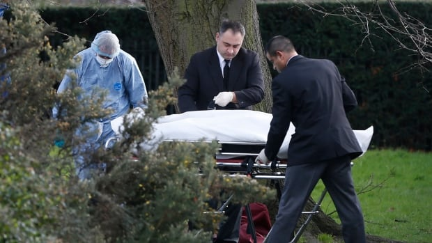 A forensic police officer and undertakers strap the body of the man to a gurney near the grounds of Kensington Palace in London on Tuesday.