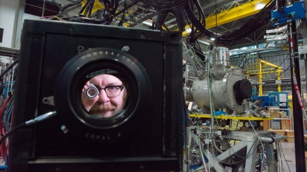 Artist in residence Blaine Campbell is seen through the lens of his 8X10 camera as poses for a portrait at the TRIUMF facility at UBC in Vancouver.