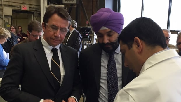 As federal ministers Scott Brison and Navdeep Bains watch, professor Pedram Sadeghian demonstrates research for improvements in concrete at a federal funding announcement Dalhousie University in Halifax.