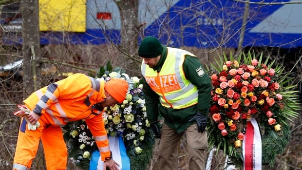 Rescue workers arrange wreaths on Wednesday in front of two trains that collided head-on near Bad Aibling, Germany. At least 10 people died in the accident on Tuesday.