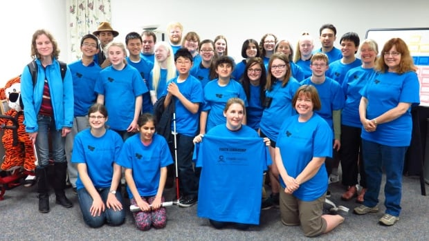 Blind Beginnings founder and executive director Shawn Marsolais (centre, holding shirt) with some of the organization's youth leaders.
