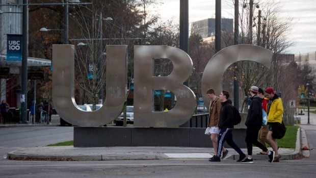 Young men walk past large letters spelling out UBC at the University of British Columbia in Vancouver, B.C., on November 22, 2015.  UBC has invited students, faculty and staff to a board of governors meeting in April.