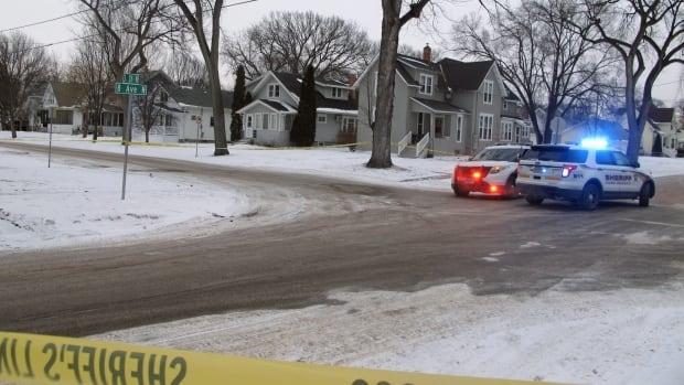 Two Cass County sheriff's deputies secure an area in North Fargo, N.D., on Thursday, one block from a house where a suspect is accused of shooting a police officer.  Officer Jason Moszer was fatally shot during a standoff with a domestic violence suspect.