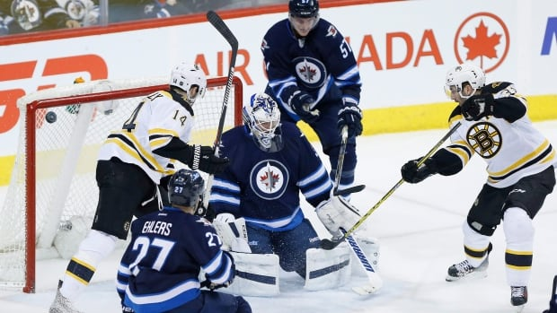 Boston Bruins' Patrice Bergeron (37) scores against Winnipeg Jets' goaltender Michael Hutchinson (34) as Jets' Nikolaj Ehlers (27) and Tyler Myers (57) defend and Bruins' Brett Connolly (14) looks on during third period NHL action in Winnipeg on Thursday, February 11, 2016.