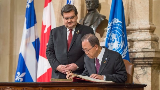 United Nations Secretary General Ban Ki-moon, right, signs the guest book as Montreal mayor Denis Coderre looks on at Montreal City Hall on Friday.