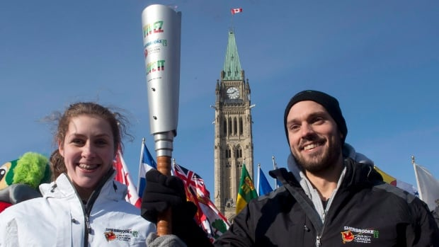 Athletes Xavier Desharnais and Raphaelle Roy Ash hold the Canada Summer Games torch after it was lit during a ceremony on Parliament Hill in Ottawa Friday February 1, 2013 in Ottawa. The City of Ottawa will bid for the 2021 Games, which will be held somewhere in Ontario.