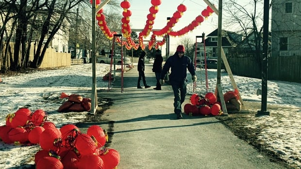Volunteers hang more than 400 Chinese lanterns hang over the Pipeline Trail on Sunday as part of the new DeLight festival.
