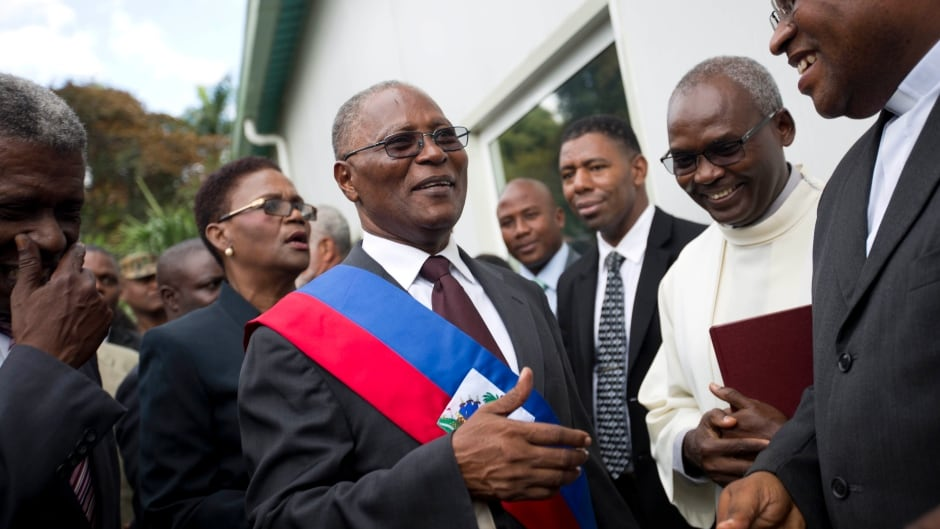 Haiti's provisional President Jocelerme Privert greets a friend during his installation ceremony in Port-au-Prince, Haiti on Feb. 14, 2016. Haitian lawmakers have chosen Privert, the country's Senate chief to lead a caretaker government that will fill the void left by the recent departure of ex-President Michel Martelly.