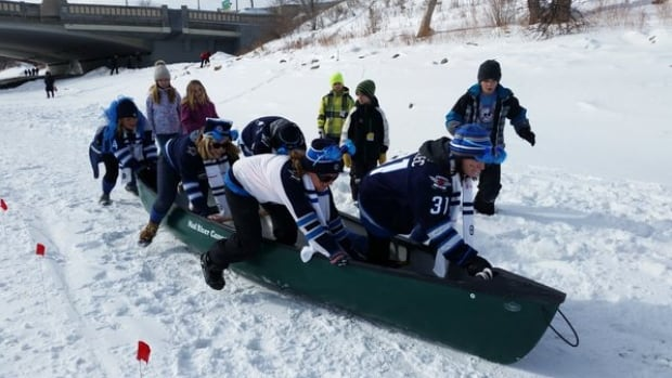 Participants in the Wild Winter Canoe Race demonstrate how ice canoeing works to onlookers.