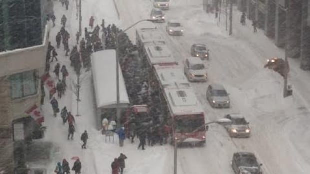People waiting for delayed buses swarm near an OC Transpo bus on Slater Street during Tuesday's afternoon commute. On Wednesday, OC Transpo's general manager says the decision to let thousands of public servants off work early caught them by surprise and contributed to the delays.