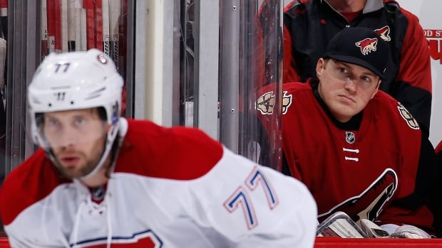 Emergency goalie Nathan Schoenfeld of the Arizona Coyotes watches from the bench during the third period of the NHL game against the Montreal Canadiens at Gila River Arena on February 15, 2016 in Glendale, Arizona. The Coyotes defeated the Canadiens 6-2.
