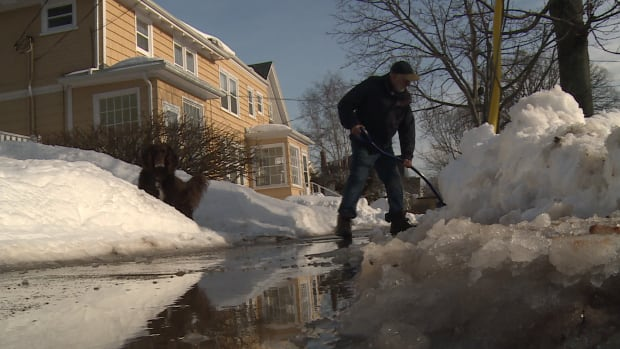 Mike MacKinnon shovels in front of his home in Charlottetown Tuesday, hoping to keep water out of his basement.