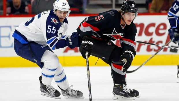 Carolina Hurricanes' Noah Hanifin, right, controls the puck in front of Winnipeg Jets' Mark Scheifele during the second period of a game on Tuesday, Feb. 16, 2016, in Raleigh, N.C. The Jets lost 2-1.