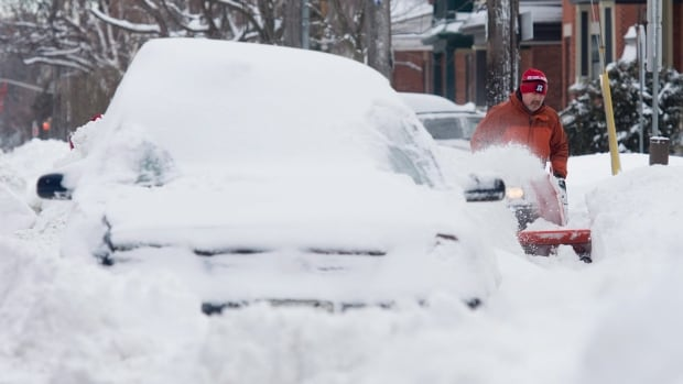 Guy Dupuis uses his snowblower Wednesday, Feb. 17, 2016 to clear the sidewalk in front of his neighbour's home following a winter storm in Ottawa.